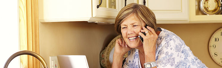 Middle-aged woman in a kitchen making a phone call about her lost hearing aid